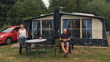 En husvagn med förtält uppsatt på en camping. En man sitter i en solstol framför och en kvinna går ut ur förtältet.