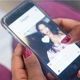 Ung kvinna kollar Instagram på mobilen.