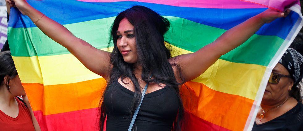 En kvinna i Libanon håller upp en regnbågsflagga.