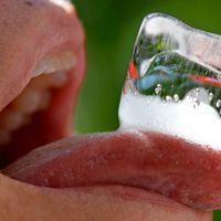 En person har en isbit på sin tunga för att svalka sig i hettan.