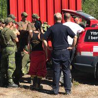 grupp personer i militärkläder och brandkläder står och pratar vid utryckningsbil