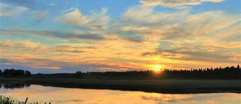 Solnedgång över Torneälven i Junosuando Norrbotten.