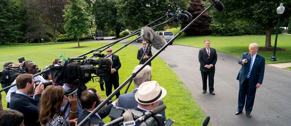 USA:s president Donald Trump på Vita husets gräsmatta framför ett pressuppbåd.
