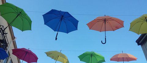 Annorlunda gatubild med uppfällda paraplyer mot en blå regnfri himmel. Fotot är taget i centrala Lidköpingl. De bara hänger där och vajar i vinden.
