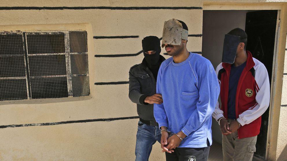 De två brittiska männen eskorteras av kurdisk militär i Kobani i Syrien där de misstänka terroristerna hållits fångna under våren. Männen bär handbojor och har täckt över sina ansikten.