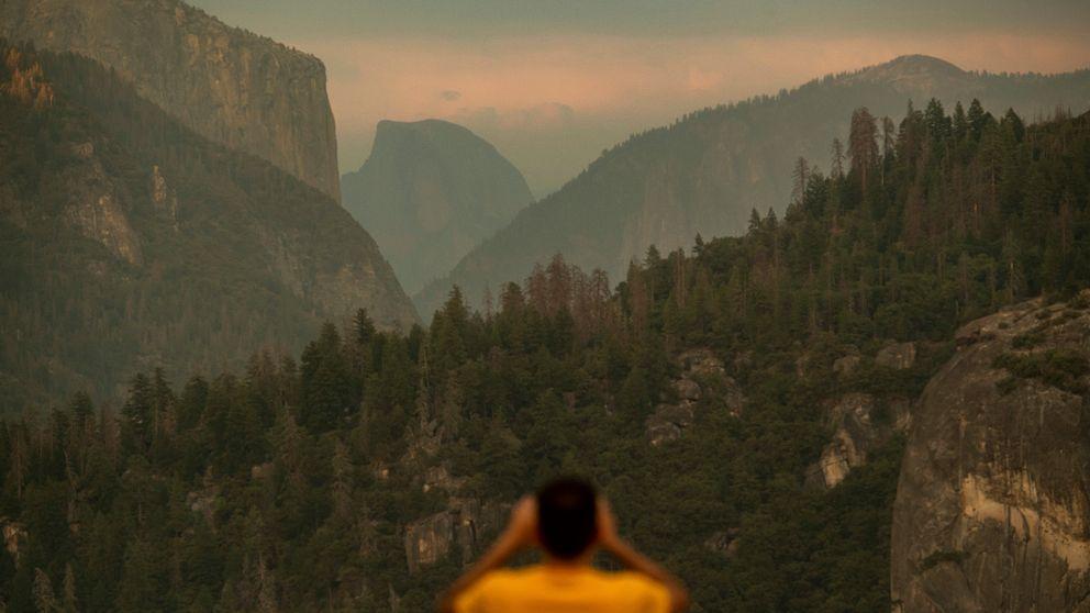 En man tittar ut över nationalparken Yosemite och man ser rök vid bergstopparna.