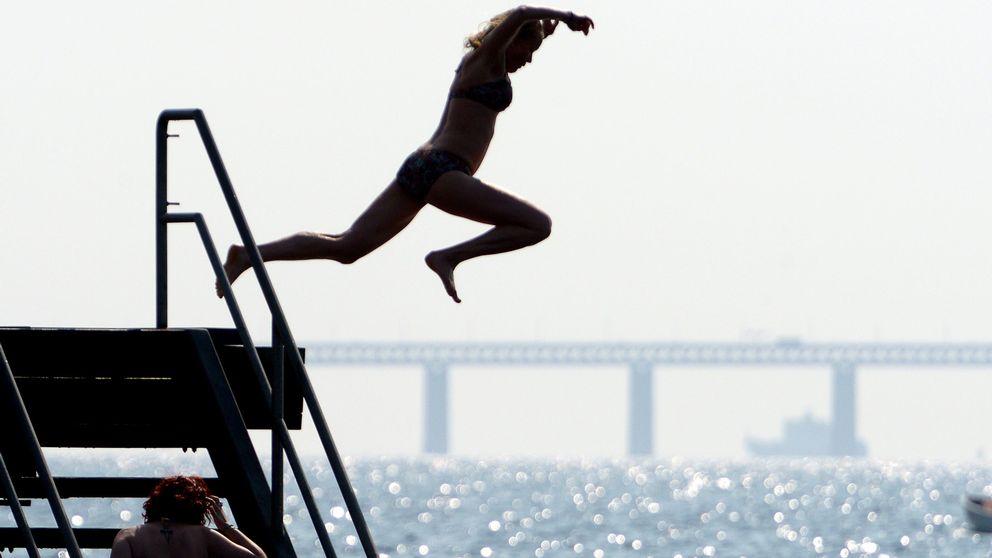En kvinna hoppar i vattnet vid Västra Hamnen i Malmö med Öresundsbron som bakgrund