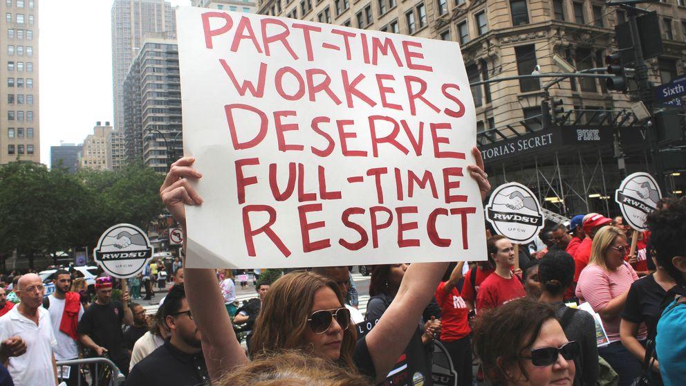 Folk som demonstrerar och bär på ett plakat med texten part-time workers deserve full-time respect