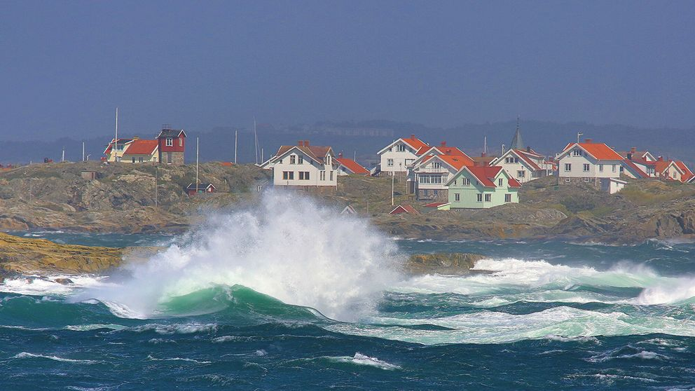 Hus vid vattnet och höga vågor.