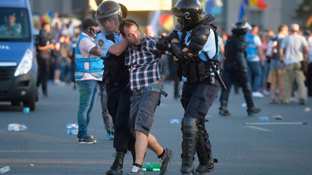 En man förs bort av två poliser.