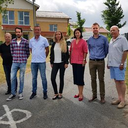 åtta föräldrar på rad framför en skolbyggnad