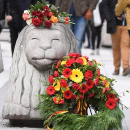 Blommor på ett betonglejon på drottninggatan i Stockholm.