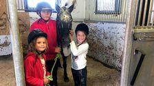 Tre hästtjejer står tillsammans med en häst i spiltan.