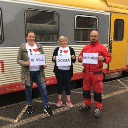 """tre protesterande med A4-papper med texten """"VI VILL OCKSÅ ÅKA MED"""" framför ett Krösatåg."""