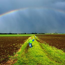 bild ur appen samt barn som springer på åker under en regnbåge