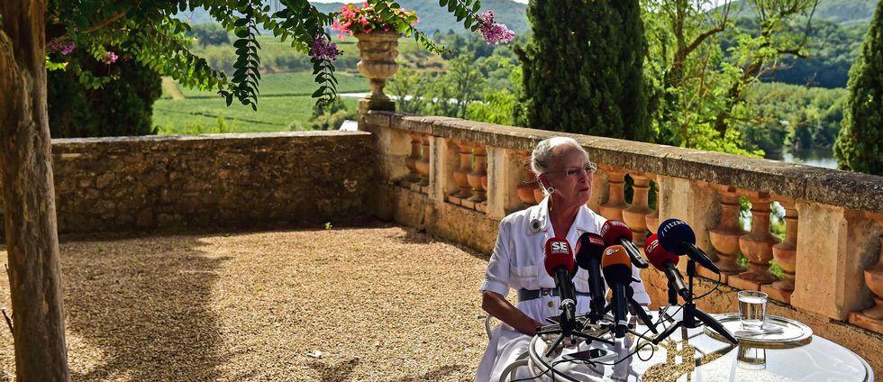 Foto på drottning Margrethe framför ett antal pressmikrofoner i den danska kungafamiljens trädgård.