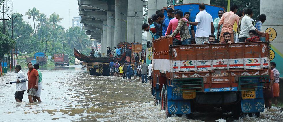 Folk åker med en lastbil till en evakueringsplats för att undkomma de kraftiga översvämningarna i staden Kochi