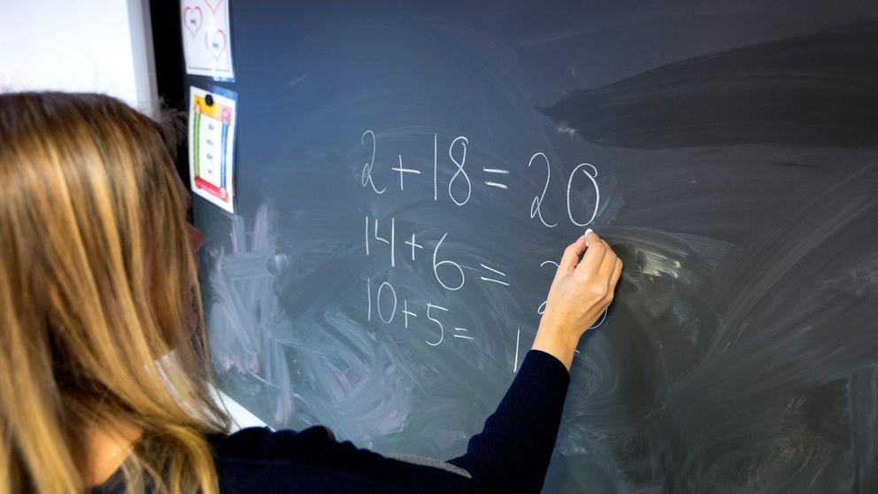 En lärare som räknar matte på tavlan.
