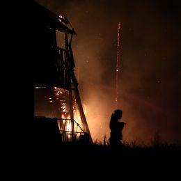 Eld. Byggnad i siluett. En kvinna går från byggnaden. Håller ett litet djur i famnen. Siluetter.