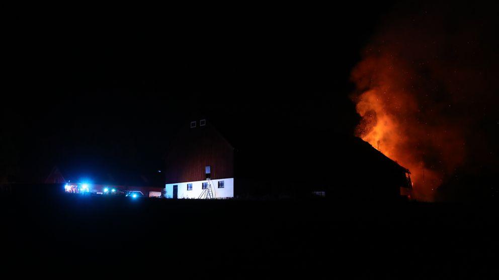 En ladugård. Mörkt runtomkring. Blå lampor från räddningsfordon. Höga orange lågor bakom byggnadens siluett.