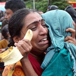 En kvinna som gråter och håller sin son i famnen.