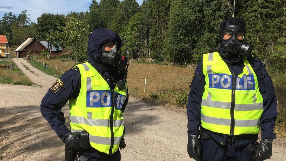 Två poliser i gasmask.