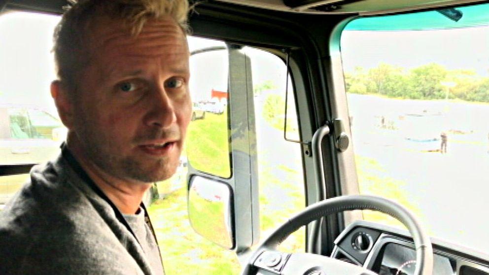 Man framför ratten i en lastbilshytt.