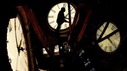 En person ställer om urverket inuti ett klocktorn