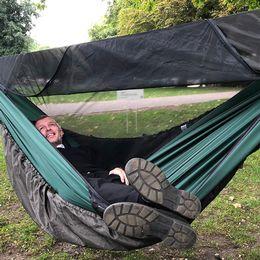 Man ligger i en hängande sovsäck med fötterna mot kameran. Han tittar upp mot himlen och ler.