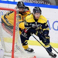 hockeyspelare åker bakom målet