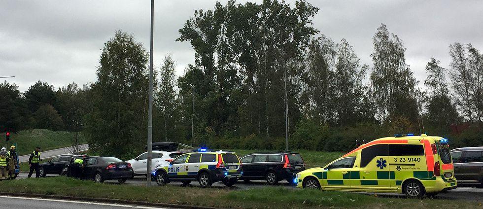 Flera personbilar, en polisbil och en ambulans stillastående på en väg.