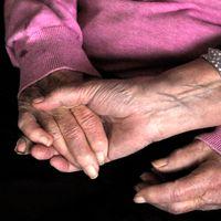 Två äldre kvinnor håller varandra i handen.