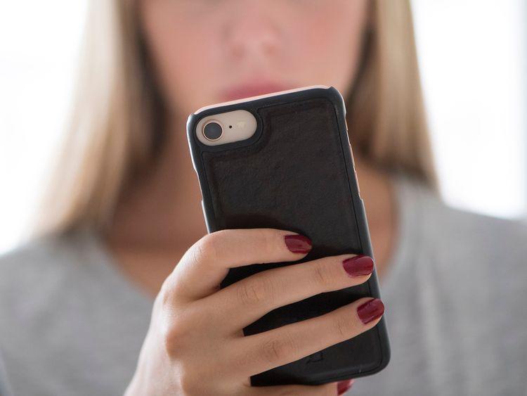 Ung tjej kollar sociala medier i mobilen.