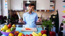 Daniel Paris ler och håller i två knivar. Framför honom står laxfilé, persilja, frukt och grönsaker.