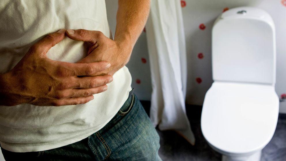 Ont i magen. En man står bredvid en toalett och håller sig om magen.