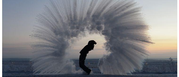 person som kastar vatten i en båge så att det fryser i luften