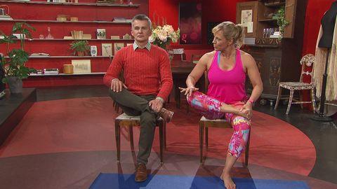 man och kvinna sitter på stolar i studion och stretchar ett ben.