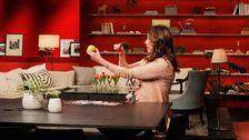 kvinna håller upp citron och chili i studion