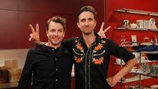 två män poserar i studion och gör v-tecken