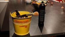 liten hink med sminkprodukter i och en sprayflaska står på bord