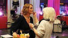 kvinna målar läpparna på annan kvinna i studion