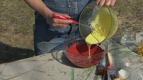 person häller ihop två olika vätskor från en skål till en annan.