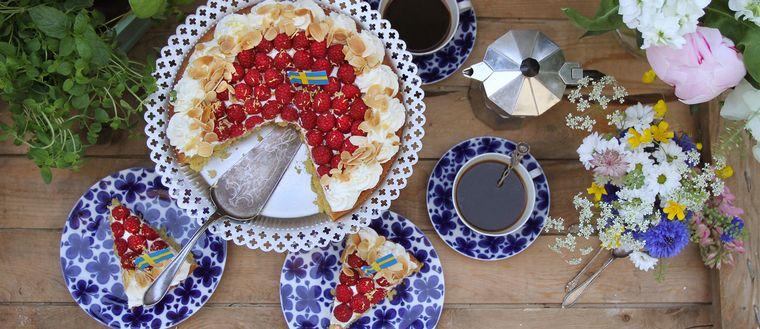 uppdukad tårta på fat och bitar på assietter, kaffekoppar, kaffekanna och blommor, ses uppifrån