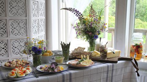 buffébord med olika rätter och sommarblommor i vas, fönster bakom