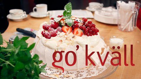 Go'kväll-logotypen över en marängtårta med bär på, på dukat bord.