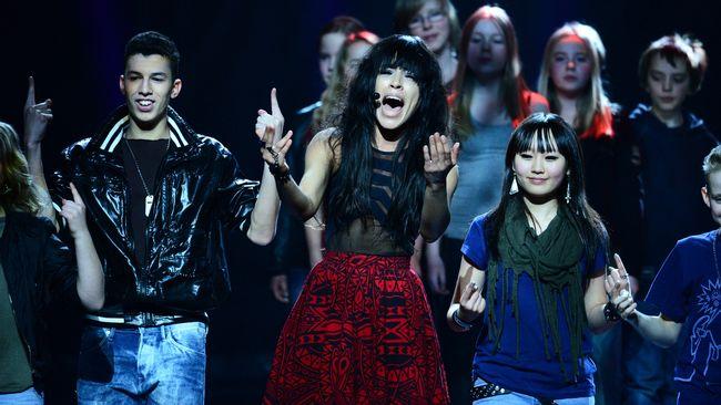 Bild på Loreen från Melodifestivalen med barnkör och teckenspråkstolkande elever.