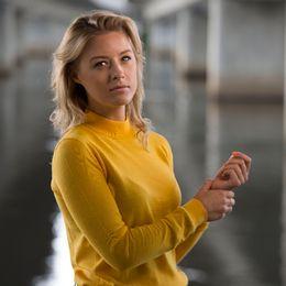 Blond kvinna i gul tröja.