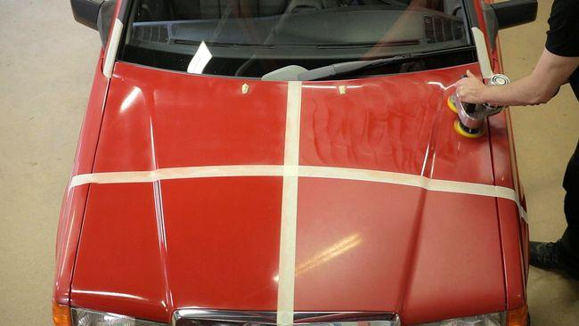 Röd bilhuv indelad i fyra lika stora partier. Till höger syns armarna från en person som arbetar med polermaskin på ett av partierna. Stor skillnad syns mellan de polerade och opolerade områdena.