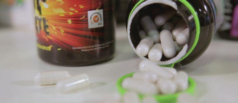 En rad pillerburkar syns suddigt i bakgrunden. I förgrunden till höger i bild ligger en öppen burk med vita piller som trillat ut över bordet.