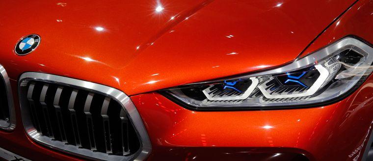 Närbild på röd bilhuv av märket BMW.